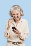 Mensaje de texto mayor irritado de la lectura de la mujer en el teléfono celular contra fondo azul Foto de archivo libre de regalías