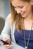 Mensaje de texto sonriente de la lectura de la mujer en el teléfono celular Imagenes de archivo