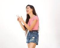 Mensaje de texto sonriente de la lectura de la mujer joven en el teléfono celular Fotos de archivo