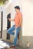 Mensaje de texto sonriente de la lectura del hombre en el teléfono móvil Foto de archivo