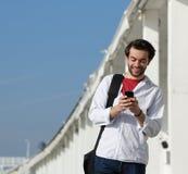 Mensaje de texto sonriente de la lectura del hombre joven en el teléfono móvil Foto de archivo libre de regalías