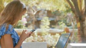 Mensaje de textos de pelo largo de la muchacha en IPhone en parque de la ciudad almacen de video