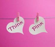Mensaje de Think Pink escrito en dos corazones blancos que cuelgan de clavijas rosadas imágenes de archivo libres de regalías