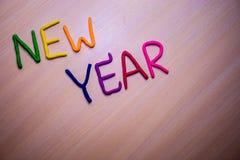 Mensaje del Año Nuevo del plasticine brillante colorido en un fondo de madera ligero Fotos de archivo libres de regalías