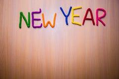 Mensaje del Año Nuevo del plasticine brillante colorido en un fondo de madera ligero Imagen de archivo libre de regalías