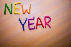 Mensaje del Año Nuevo del plasticine brillante colorido en un fondo de madera ligero Imágenes de archivo libres de regalías