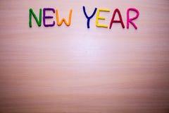 Mensaje del Año Nuevo del plasticine brillante colorido en un fondo de madera ligero Foto de archivo