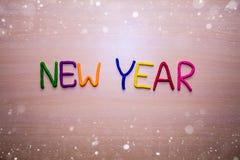 Mensaje del Año Nuevo del plasticine brillante colorido en un fondo de madera ligero con nieve Fondo brillante colorido del Año N Fotos de archivo libres de regalías