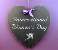 Mensaje del día de las mujeres internacionales escrito en la pizarra de la dimensión de una variable del corazón Foto de archivo