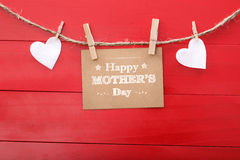 Mensaje del día de madres con los corazones del fieltro que cuelgan con las pinzas Fotos de archivo libres de regalías