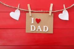 Mensaje del día de padres sobre el tablero de madera rojo Imagenes de archivo