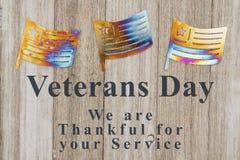 Mensaje del día de veteranos con las banderas del metal en la madera imágenes de archivo libres de regalías