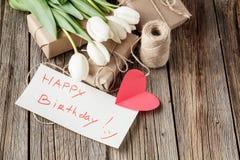 Mensaje del feliz cumpleaños con las flores en la tabla rústica con las flores Foto de archivo libre de regalías