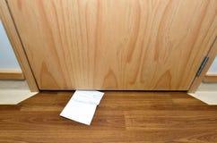 Mensaje deslizado debajo de puerta imagen de archivo