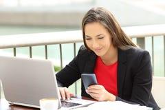 Mensaje ejecutivo de la lectura en un teléfono al aire libre imagen de archivo libre de regalías