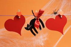 Mensaje en blanco del feliz Halloween para su texto aquí en corazones rojos y gato negro con las clavijas que cuelgan de una línea Foto de archivo