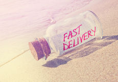 Mensaje en una botella con el texto 'entrega rápida' Imágenes de archivo libres de regalías