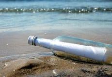 Mensaje en una botella de cristal en orilla de la arena Fotos de archivo