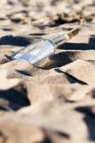Mensaje en una botella en la arena imagenes de archivo