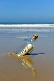 Mensaje en una botella en la orilla de la playa, pregunta, porqué Foto de archivo libre de regalías