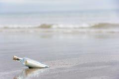 Mensaje en una botella enterrada en arena Foto de archivo libre de regalías