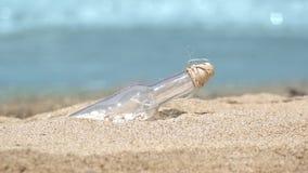 Mensaje en una botella en la playa tropical de la isla exótica, ondas de la turquesa del mar en fondo metrajes