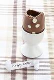 Mensaje feliz de pascua con el huevo de chocolate comido mitad Fotografía de archivo libre de regalías