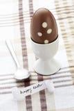 Mensaje feliz de pascua con el huevo y la cuchara de chocolate Fotos de archivo libres de regalías