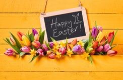 Mensaje feliz de Pascua con los tulipanes frescos de la primavera Imagen de archivo libre de regalías