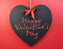 Mensaje feliz del día de tarjeta del día de San Valentín escrito en la pizarra del corazón. Fotografía de archivo