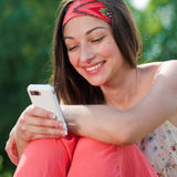 Mensaje feliz joven de la lectura de la mujer en móvil Foto de archivo libre de regalías