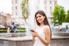 Mensaje joven de la escritura de la mujer de la belleza en el teléfono celular en un café de la calle Fotos de archivo