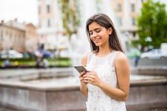 Mensaje joven de la escritura de la mujer de la belleza en el teléfono celular en un café de la calle Fotos de archivo libres de regalías