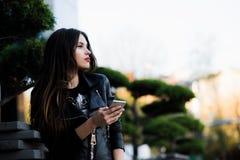 Mensaje joven de la escritura de la mujer de la belleza en el teléfono celular en un café de la calle Mirada abajo Fotografía de archivo