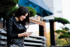 Mensaje joven de la escritura de la mujer de la belleza en el teléfono celular en un café de la calle Mirada abajo Fotos de archivo