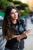 Mensaje joven de la escritura de la mujer de la belleza en el teléfono celular en un café de la calle Mirada abajo Foto de archivo libre de regalías