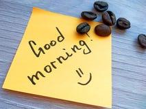 Mensaje manuscrito de la buena mañana en nota pegajosa anaranjada con los granos de café en fondo de madera fotografía de archivo