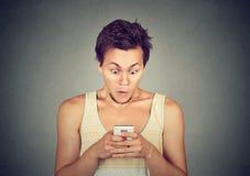 Mensaje o noticias chocado de texto de la lectura del hombre en el teléfono móvil Imagenes de archivo
