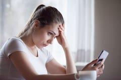Mensaje que consigue decepcionado trastornado de la mujer joven mún en smartphone foto de archivo libre de regalías