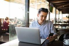 Mensaje que manda un SMS asiático joven del hombre de negocios en el medios uso social del profesional casual del teléfono Trabaj Foto de archivo libre de regalías