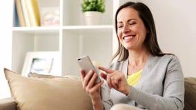 Mensaje que manda un SMS de la mujer feliz en smartphone en casa almacen de metraje de vídeo
