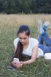 Mensaje que manda un SMS de la mujer hermosa triste joven en el teléfono móvil en urb Fotografía de archivo libre de regalías