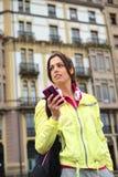 Mensaje que manda un SMS de la mujer urbana deportiva en smartphone en calle Imagen de archivo