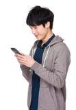 Mensaje que manda un SMS del hombre asiático joven en su teléfono móvil fotos de archivo