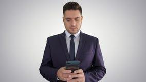 Mensaje que manda un SMS del hombre de negocios serio en su teléfono en fondo de la pendiente metrajes