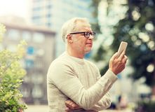 Mensaje que manda un SMS del hombre mayor en smartphone en ciudad imagenes de archivo