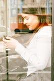 Mensaje que manda un SMS femenino en café Imagen de archivo
