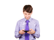 Mensaje que mecanografía al amigo El muchacho adolescente hermoso que sostenía el teléfono móvil y que lo miraba aisló en blanco fotografía de archivo