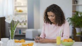 Mensaje que mecanografía de la muchacha multirracial en el teléfono móvil, hora de la almuerzo sana, juicing almacen de metraje de vídeo