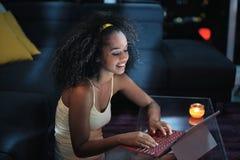 Mensaje que mecanografía de la mujer joven de Latina en el ordenador portátil en la noche Fotos de archivo libres de regalías